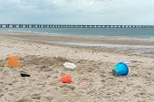 picture of bucket  - Sand castle buckets let sitting in the sand on the Chesapeake Bay in Virginia Beach Va - JPG