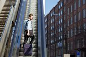 stock photo of escalator  - Portrait of a young man walking up escalator with travel bags - JPG