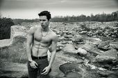 stock photo of shirtless  - Athletic shirtless young man outdoor at river or water stream in black and white photo - JPG