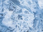 stock photo of ice crystal  - beautiful crystal patterns on the surface of the clear blue brittle ice on the lake in the winter in December before Christmas - JPG