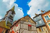stock photo of timber  - Old traditional wooden half timbered facades and church in Honfleur - JPG