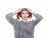 stock photo of beanie hat  - funky girl in knit sweater and hat holding her hair and smiling - JPG