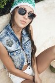 stock photo of vest  - Woman in sunglasses and handmade denim vest looking at the camera  - JPG