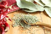 stock photo of bay leaf  - Wooden spoonful of dried rosemary and bay leaf - JPG