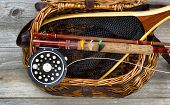 pic of fly rod  - Antique fly fishing reel rod flies and net on top of open creel with rustic wood underneath - JPG