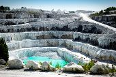 stock photo of open-pit mine  - View of the rocky layers of a large and impressive open pit white marble stone mine - JPG