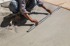 stock photo of wet  - Construction worker spreading wet concrete on the ground - JPG