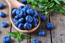 stock photo of peppermint  - Organic fresh blueberries with peppermint on a wooden background - JPG