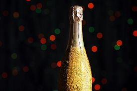 foto of champagne color  - Decorative champagne bottle on dark colorful spotted background - JPG