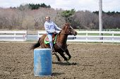 pic of barrel racing  - A teenage girl turns around a barrel and races to the finish line - JPG