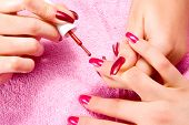 Young woman with beautiful long nails make the manicure pic.