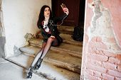 Young Goth Girl On Black Leather Skirt And Jacket Sitting On Stairs Of Old House, Listening Rock Mus poster