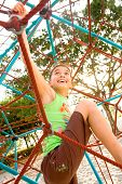 stock photo of spider web  - Active young girl climbing the spider web playground activity in summer - JPG