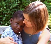 image of babysitting  - young caucasian woman holding a young african american child - JPG