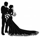 stock photo of wedding couple  - A bride and groom on their wedding day about to kiss in silhouette - JPG