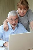 pic of elderly couple  - Senior couple using laptop computer at home - JPG