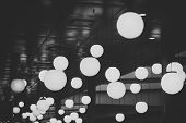 Many Round Chandeliers And Lamps Under Ceiling. Glowing Lamps In Dark Fashionable Interior, Defocuse poster