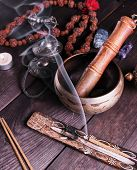 Copper Singing Bowl And A Wooden Stick On A Brown Table, A Stick With Incense Is Burning Nearby poster