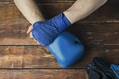 Mans Hand In Boxing Bandages And A Boxing Glove On A Wooden Background. The Concept Of Training For  poster