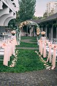 Beautiful Wedding Set Up. Area Of The Wedding Ceremony. Round Arch, White Chairs Decorated With Flow poster