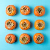 Delicious Fresh Persimmon Fruits On Blue Background. poster
