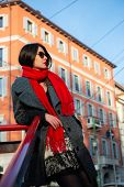 Attractive young woman wearing gray coat with long dark hair red scarf and with sun glasses posing o poster
