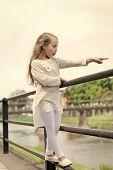 Kid Girl With Long Hair Walks Near Riverside, River On Background. Girl Child Tourist Enjoy Sightsee poster