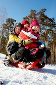 stock photo of toboggan  - Happy friends in winterwear tobogganing in park - JPG