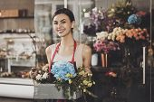 Portrait Of Beautiful Girl Florist In Flower Shop. Young Smiling Girl Florist Collects Flower Basket poster