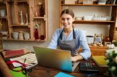 Portrait Of Female Small Business Owner Using Laptop And Looking At Camera In Shop, Copy Space poster