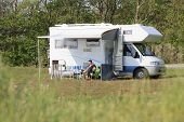 pic of campervan  - Woman sitting outside a campervan reading in the sun - JPG