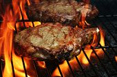 image of barbecue grill  - Two Juicy stakes grilling on the barbecue with lots of flame licking around them