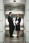 stock photo of elevators  - Happy business colleagues communicating in elevator - JPG
