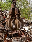 stock photo of scrap-iron  - inustrial machine with scrap metal grapple in front of scrap iron - JPG