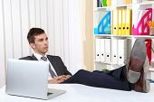 image of table manners  - Businessman resting at his office with his shoes on table - JPG