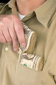 stock photo of tuck-shop  - A man places wads of cash into his shirt pocket - JPG