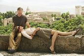 Happy middle aged couple relaxing on wall overlooking Granada; Spain