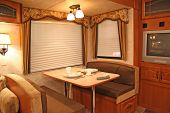 stock photo of motor coach  - interior of a motor home showing dining table with dishes - JPG