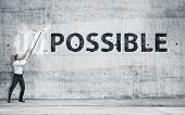 "stock photo of impossible  - Man turning the word ""Impossible"" into ""Possible""