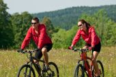 Young Man And Woman Riding Mountain Bike