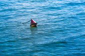stock photo of conic  - Red colored chained conical buoy floating at the water surface - JPG