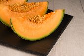 foto of honeydew melon  - Juicy honeydew melon on a black slate tray.