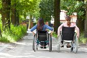 pic of wheelchair  - Back view of two women on wheelchairs in park - JPG