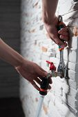 stock photo of adjustable-spanner  - Closeup portrait of plumbers hands mounting a flexible pipe to a tap with adjustable spanner monkey wrench on grey stone wall - JPG