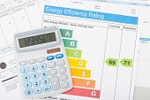 stock photo of fuel efficiency  - Calculator with utility bill and energy efficiency chart - JPG