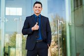 stock photo of laws-of-attraction  - Attractive young businessman giving a thumb up as a sign of approval and smiling - JPG