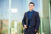 picture of laws-of-attraction  - Handsome Hispanic man in a suit carrying his resume and waiting for a job interview and smiling - JPG