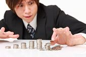pic of japanese coin  - stack of coins collapsed when businessman put a coin - JPG