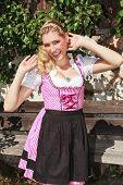 stock photo of flirty  - Flirty blond bavarian girl in dirndl smiles seductively into the camera - JPG