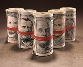 picture of gag  - Money rolls with elastic gagging the mouths of the symbols of United States currency - JPG